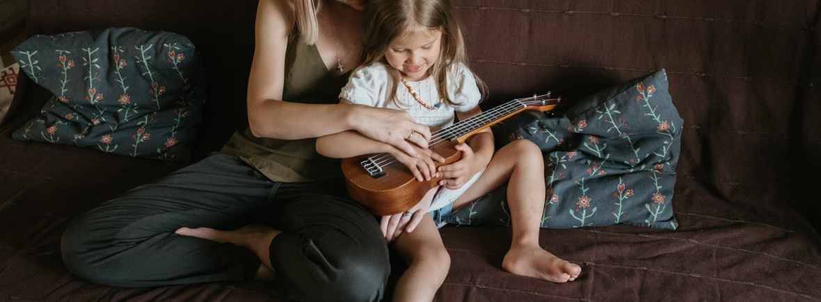 mom and daughter, child playing guitar